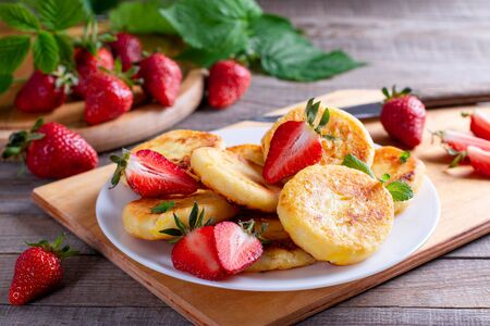 Cottage cheese pancakes or syrniki with sliced strawberry on white plate for breakfast. Healthy breakfast.