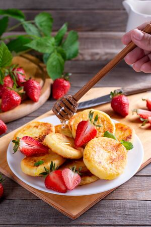 Cottage cheese pancakes with strawberry on a white plate on a wooden table. Breakfast or Lunch Concept.