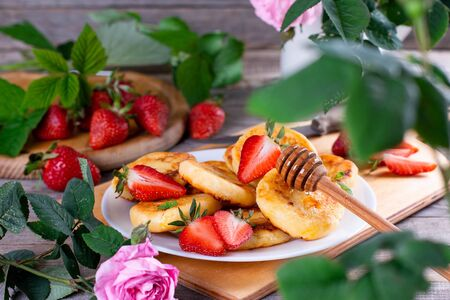 Cottage cheese pancakes or syrniki with sliced strawberry on a white plate on a wooden table with summer flowers for breakfast. Healthy breakfast. Archivio Fotografico