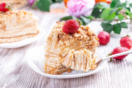 Piece of cake Napoleon on white plate . Russian cuisine, layered cake with pastry cream, close up view