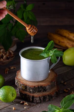Healthy fresh green smoothie on rustic wooden background. Blended smoothie with ingredients