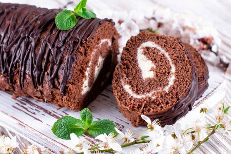 Delicious chocolate roll sponge cake with vanilla cream, mint leaves and spring flowers. Desert sweet food Archivio Fotografico