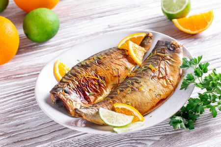 Gourmet Food: Baked fish with lime and orange slices with orange sauce on a plate close-up. Horizontal