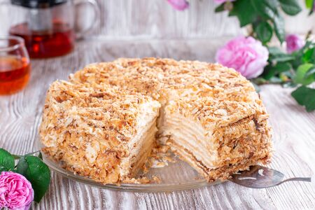 Classic Napoleon cake with a cup of tea. Traditional millefeuille dessert with puff pastry and custard, russian cuisine treat Archivio Fotografico