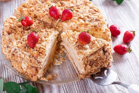 Sliced Napoleon cake on a white wooden table. Classic dessert