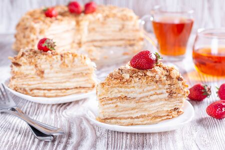 Two pieces of cake Napoleon on white plate. Russian cuisine, multi layered cake with pastry cream, close up view