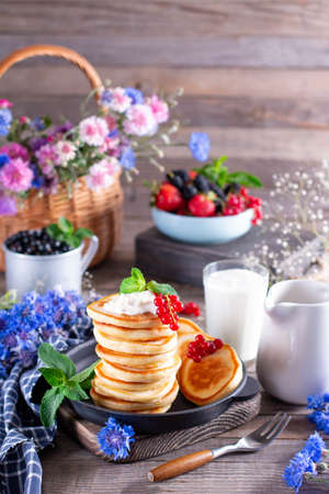 Healthy summer breakfast, pancakes with fresh berry and sour cream on a wooden table