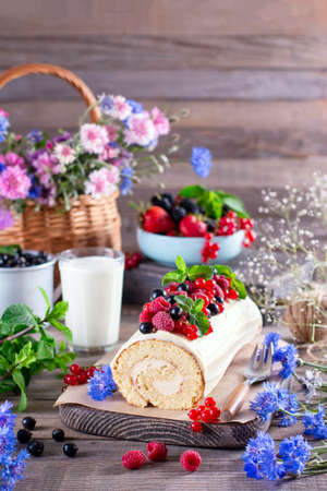 Biscuit roll with mascarpone cream and berries, mint leaves on wooden background. Summer food concept 新聞圖片