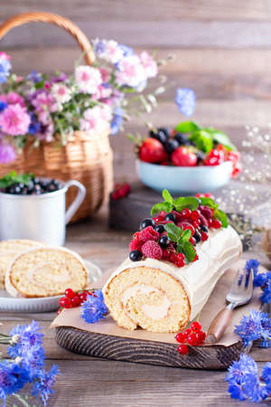 Sweet sponge biscuit roll with mascarpone cream and berries, mint leaves on wooden background. Summer food concept 新聞圖片
