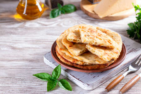 Baked dough tortilla with cheese in a ceramic plate on a wooden table. Place for text
