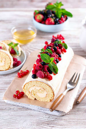 Sponge cake roll filling cream and berries, strawberry, raspberries, blueberry and red currants on white wooden background. Soft focus. Summer food concept 新聞圖片