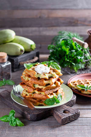 Zucchini waffle, zucchini fritters cooking on waffle maker with sour cream with basil on a plate. Vertical 版權商用圖片