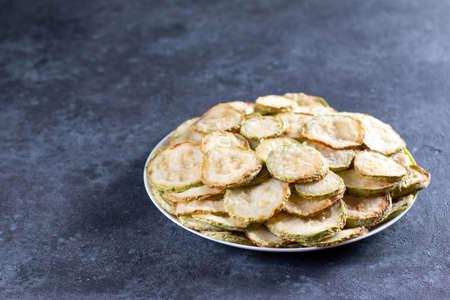 Fried zucchini in a plate on a dark concrete background 版權商用圖片