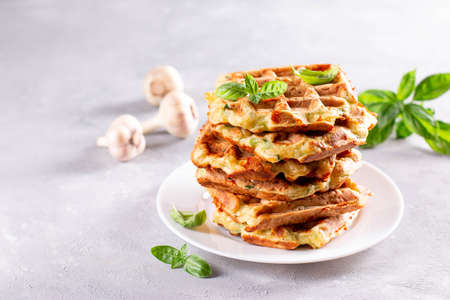 Zucchini waffle, zucchini fritters cooking on waffle maker, vegetarian zucchini waffles with basil and garlic on a plate. Copy space 版權商用圖片