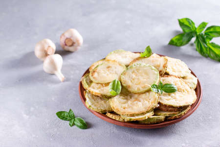 Zucchini, fried in batter in a plate on a light background 版權商用圖片
