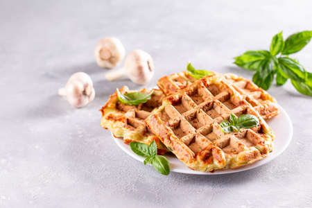 Zucchini waffle, zucchini fritters cooking on waffle maker, vegetarian zucchini waffles with basil and garlic in a plate