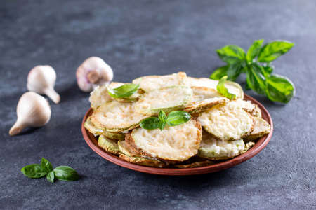 Zucchini, fried in batter with basil in a plate on a dark concrete background 版權商用圖片