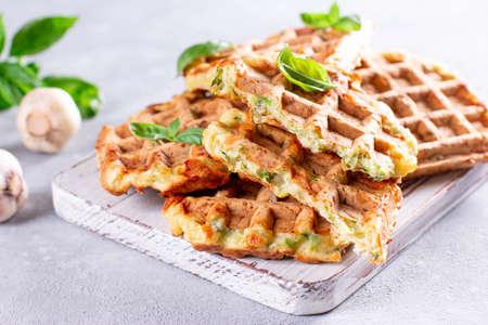 Zucchini waffle, zucchini fritters cooking on waffle maker, vegetarian zucchini waffles with basil and garlic on a white board on a light background 版權商用圖片