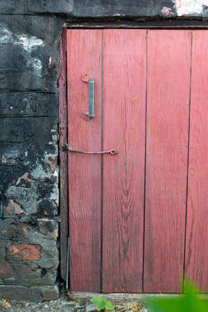 Wooden old pink doors in the wall of an old house. Selective focus 版權商用圖片