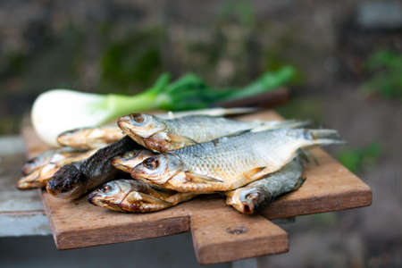 Dried salted fish on a wooden board, a great appetizer for beer on dark wooden boards