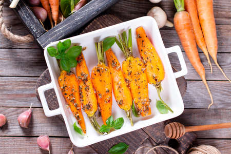 Fried carrots with green herbs in baking tray, close up Reklamní fotografie