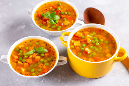 Vegetable soup with spices in a yellow saucepan on a light stone background. Healthy food