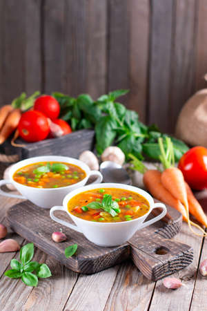Vegetable soup in a white bowl on a wooden board on the table. Vegetarian soup. Healthly food