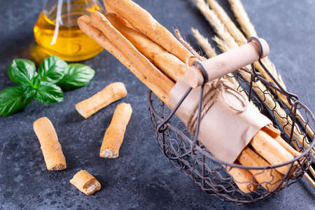Grissini bread sticksi or salted bread sticks and bread lying in a metal basket on a dark background. Fresh italian snack
