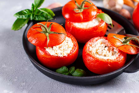Stuffed tomatoes with cheese and basil a on light concrete background Reklamní fotografie