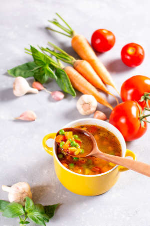 Vegetable soup in a yellow saucepan on a light stone background. Healthy food Reklamní fotografie