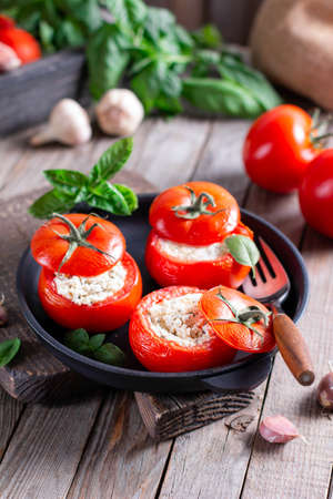 Three stuffed tomatoes with cheese and basil in a frying pan on a wooden table. Delicious snack