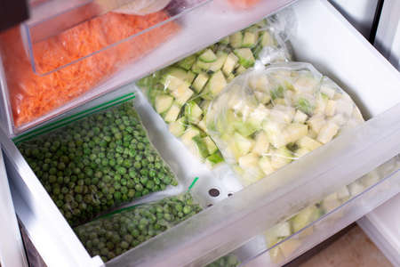 Plastic bags with different frozen vegetables in refrigerator. Zucchini and green pea, closeup Reklamní fotografie