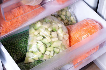 Bags with frozen vegetables in refrigerator. Frozen Zucchini closeup Reklamní fotografie