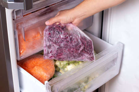 Man taking plastic bag with beet from refrigerator, closeup