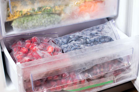 Frozen ecological berries in reusable plastic bags: strawberry and blueberry. Berries on the freezer shelves.