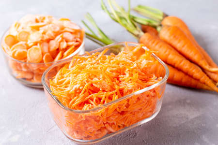 Frozen grated carrots in a glass container on a light background. Frozen vegetables Foto de archivo