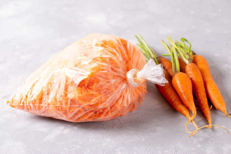 Frozen grated carrots in plastic bags on a light background. Frozen vegetables