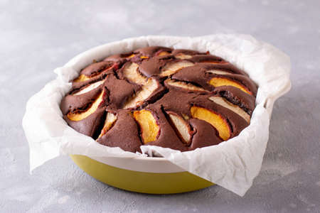 Ready homemade pie in a baking dish with peaches. Cooking chocolate cake