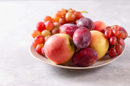 Composition with fruits. Grapes, apples and plums in a plate. Copy space. Reklamní fotografie