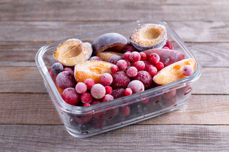 Frozen mixed fruits-berries in a glass container on a wooden table. Selective focus Zdjęcie Seryjne