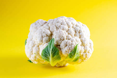 Fresh cauliflower on yellow background. Seasonal vegetables minimal style. Food in minimal style.