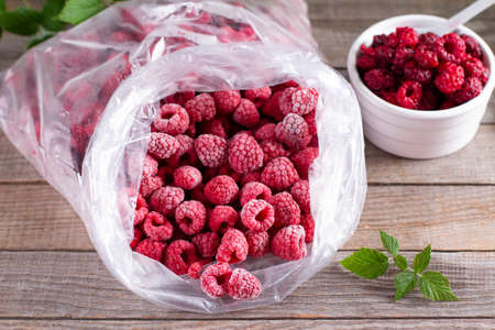 Frozen raspberries in a plastic bag on a wooden background