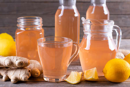 Kombucha or cider fermented drink. Cold tea beverage with beneficial bacteria, ginger, lemon on wooden background. For healthy nutrition.
