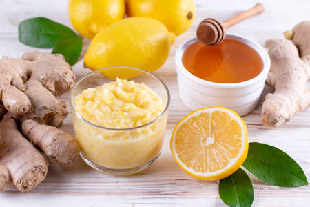 Fall immune system booster - ginger, lemon and honey on a white wooden table