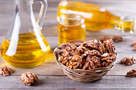 Walnut oil with nuts on a wooden background. Change traditional oil