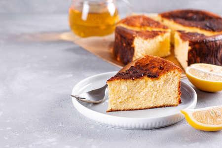 Piece of San Sebastian Basque Cheesecake on the plate on a light background. Copy space Reklamní fotografie