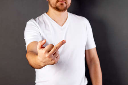 Man shows off gesture to camera. Middle finger, offensive gesture. Fuck you concept.