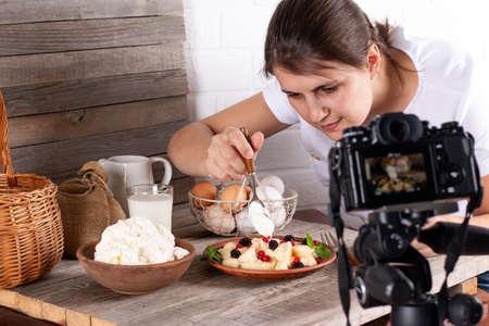 Woman shooting food on table with camera. Female photographer taking pictures of sweet food, camera mounted on tripod