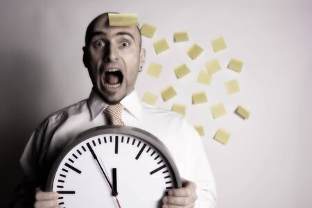 uptight: Frantic, unorganized businessman unsuccessfully tries to use many post-it notes to remind him of his busy schedule and appointments.  Stock Photo