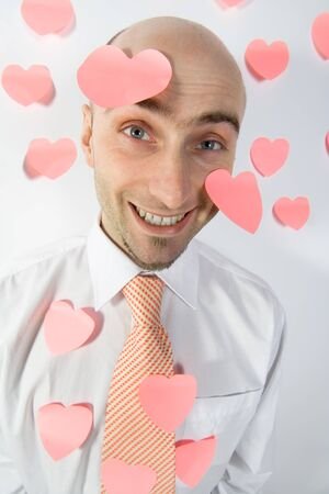A smiling businessman uses pink, heart-shaped post-it notes to remind him of Valentine's Day.  Stock Photo - 1498119